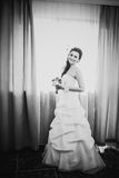 Black white photography beautiful young happy  bride standing near the window Stock Photos