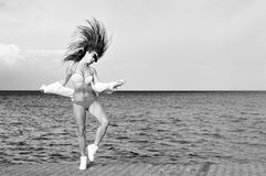 Black white photography of beautiful young lady enjoying dancing jumping over outdoors water sky background Royalty Free Stock Photo