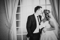 Black white photography  bride and groom posing in a hotel room on background windows Stock Images