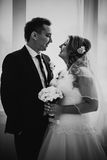 Black white photography bride and groom posing in a hotel room on background windows Royalty Free Stock Image