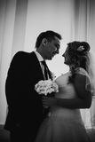 Black white photography bride and groom posing in a hotel room on background windows Royalty Free Stock Images