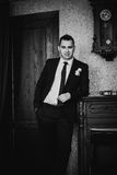 Black white photography elegance groom  is posing on the background room Stock Photography