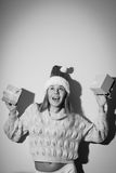 Black and white photography of exciting pretty. Portrait of exciting beautiful girl in Santa hat with gifts. Black and white photography Stock Images