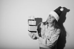 Black and white photography of exciting pretty. Portrait of exciting pretty girl in Santa hat with gifts. Black and white photography Royalty Free Stock Images