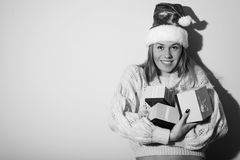 Black and white photography of exciting pretty. Portrait of exciting pretty girl in Santa hat with gifts. Black and white photography Royalty Free Stock Image