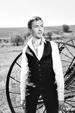 Black and white photography. A handsome young man. In a waistcoat, standing next to a haymaking machine in the field Stock Photography