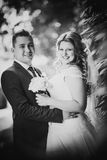 Black white  photography happy couple bride and groom embracing they stand on background Stock Images