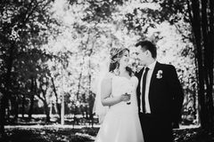 Black white photography happy couple bride and groom embracing they stand in a forest Stock Image
