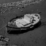 Black & White Photography of a Mediterranean Fishing Boat on the Beach caused by the Low Tide in Euboea - Nea Artaki, Greece Royalty Free Stock Image