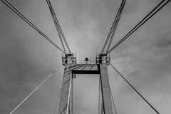 Atmospheric black and white photography of a piece of bridge. Black and white photography of a piece of bridge with slings on cloudy background Stock Images