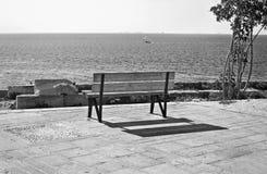 Black and white photography Piraiki Piraeus Greece. Park bench in front of the sea Stock Photos