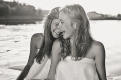 Black white photography of two happy girls playing in water at the sunset beach. Sun flare background. Black and white photography of two happy girls playing in Stock Photos