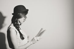 Black white picture of beautiful girl reading a book against light wall background Royalty Free Stock Image