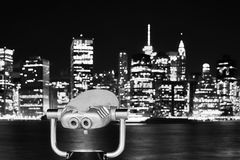 Binoculars pointed at Manhattan skyline at night, NYC. Black and white picture of binoculars pointed at Manhattan skyline at night, New York City, USA Royalty Free Stock Photo