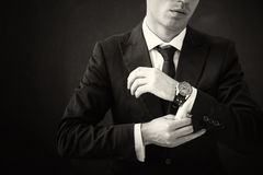 Black and white picture of business man fixing his shirt Stock Photos