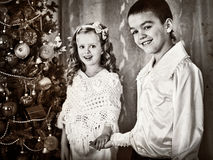 Black and white picture children under Christmas tree. Christmas retro style. Old picture. Brother and sister meet Christmas Royalty Free Stock Photos