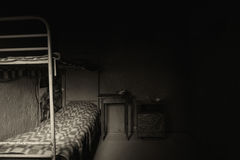 Black and white picture of dark empty prison cell with iron bunk Stock Image