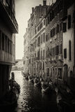 Black and white picture of gondolas near of the buildings in the Venice narrow channel Royalty Free Stock Images