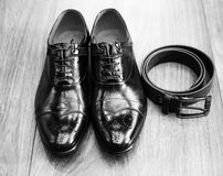 Black and white picture of male stylish accessories for solemn e. New black man shoes and black belt on wooden brown surface of floor. Black and white picture of Stock Image