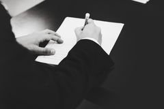 A black and white picture of a man signing papers.  Royalty Free Stock Photography