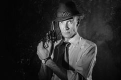 Black and white picture of private detective with gun in both hands. Agent stay front to camera. Criminal scene. Studio Stock Photography