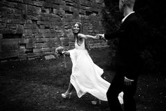 A black and white picture of a stunning bride walking along the Stock Photography