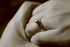 Black and white picture of two hands touching each other with wedding rings on black background royalty free stock images