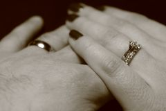 Black and white picture of two hands touching each other with wedding rings on black background royalty free stock photography