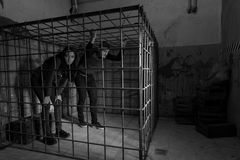 Black and white picture of victims imprisoned in a metal cage tr Royalty Free Stock Photo