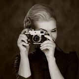 Black and white picture of a woman with camera Stock Photography