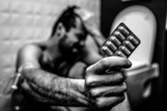 Black and white picture of young man sit on floor in rest room and hold plate of pills. Hand is wrapped with plait for royalty free stock photos