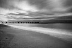 Black and white Pier. Black and white image of waves crashing on a beach in Miami stock image