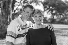 Black and white portrait of American senior beautiful and happy mature couple around 70 years old showing love and affection smili. Ng together in the park Royalty Free Stock Photography