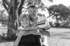 Black and white portrait of American senior beautiful and happy mature couple around 70 years old showing love and affection smili. Ng together in the park Stock Photos