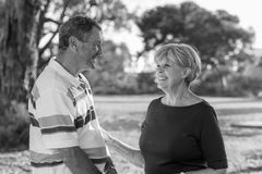 Black and white portrait of American senior beautiful and happy mature couple around 70 years old showing love and affection smili. Ng together in the park Royalty Free Stock Images
