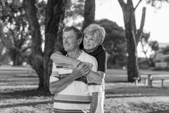 Black and white portrait of American senior beautiful and happy mature couple around 70 years old showing love and affection smili. Ng together in the park Royalty Free Stock Photo