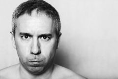 Portrait of angry unhappy dissatisfied aggressive middle-aged man. Black and white portrait of angry unhappy dissatisfied scary naked middle-aged man royalty free stock photo