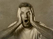 Black and white portrait of attractive man in shock and surprised with hands on face alarmed with mouth and eyes wide open in disb. Elief and surprise expression Stock Photos