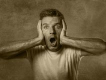 Black and white portrait of attractive man in shock and surprised with hands on face alarmed with mouth and eyes wide open in disb. Elief and surprise expression Stock Image