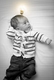 Black and white portrait of baby boy with glowing light bulb ove Stock Photos