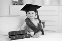 Black and white portrait of baby boy in graduation sitting with Stock Images