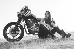 Black-and-white portrait of a beautiful biker woman sitting by her motorcycle Royalty Free Stock Image