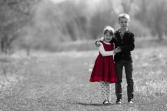 Black and white portrait of beautiful children in new clothes st. Anding together outdoors on bright blurred background, older brother embracing protectively royalty free stock photo