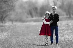 Black and white portrait of beautiful children in new clothes st. Anding together outdoors on bright blurred background, older brother embracing protectively stock photography