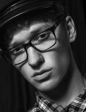 Black and white portrait of a beautiful dark-haired guy wearing glasses and a cap Stock Photos