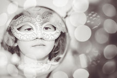 Black and white portrait of a beautiful girl in carnival mask lo. Oking into a mirror. Retro style Stock Photo