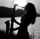 Black and white portrait of beautiful girl playing the saxophone at the lake Royalty Free Stock Photo