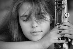 Black and white portrait of a beautiful girl with a saxophone on a lawn Royalty Free Stock Images