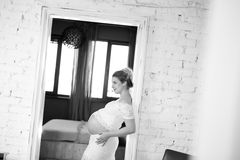 Black and white portrait of a beautiful pregnant woman at home Stock Photography