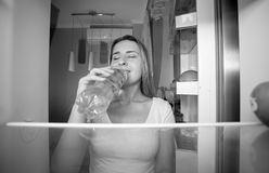 Black and white portrait of beautiful smiling woman taking water. From fridge and drinking it. View from inside of open refrigerator Royalty Free Stock Images